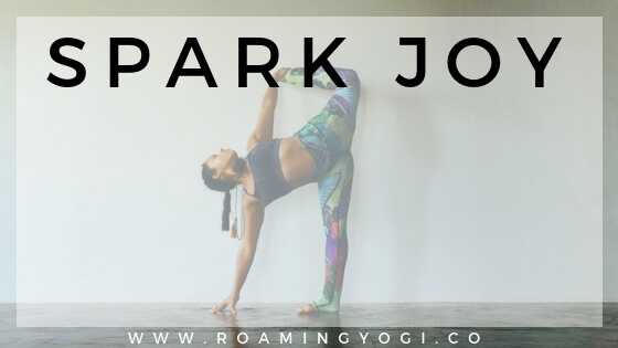 Yoga pose image with text overlay: Spark Joy. www.roamingyogi.co