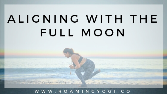 Image of a young woman in a standing yoga pose in front of the ocean and sunrise with text overlay: Aligning With the Full Moon. www.roamingyogi.co