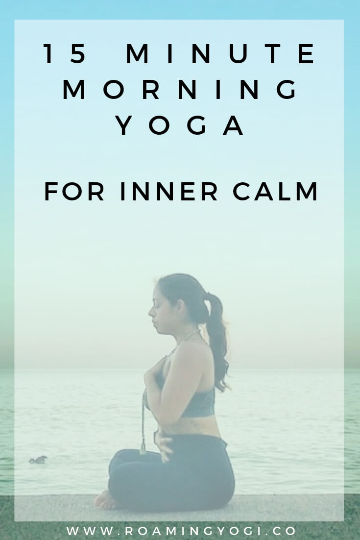 Image of a young woman in a seated meditation pose with one hand over her heart and one hand over her belly, with text overlay: 15 Minute Morning Yoga for Inner Calm. www.roamingyogi.co