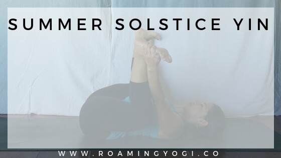 Image of a young woman in the yoga pose Happy Baby, with text overlay: Summer Solstice Yin Yoga. www.roamingyogi.co